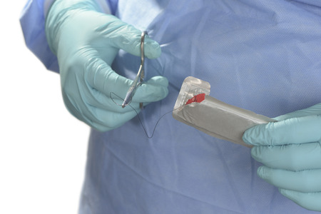 suture: Operating room technician prepares suture for use with needle holder.