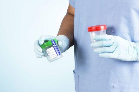 samples: Nurse holds two sterile specimen cups on blue background.