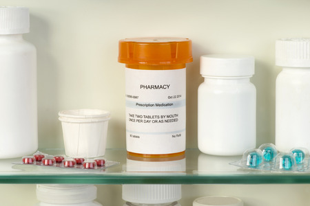 Prescription bottle on medicine cabinet shelf.
