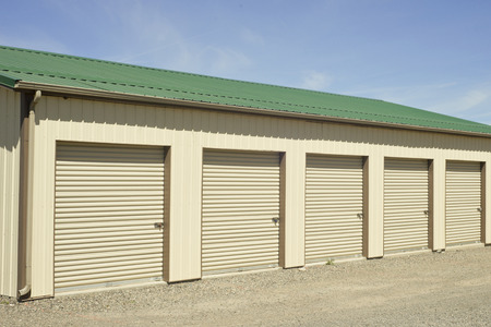 self storage: Green and beige outdoor self storage units. Stock Photo