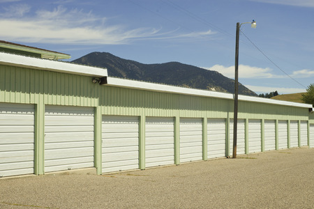 self storage: Green and white outdoor self storage units with security light.