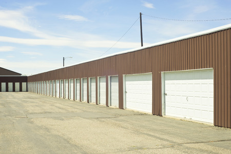 self storage: Brown and white outdoor self storage units with security light.
