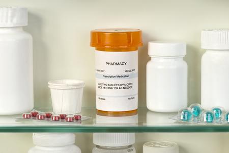 medicine cabinet: Prescription bottle on medicine cabinet glass shelf with medications.