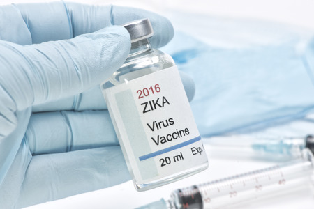 epidemiology: Hypothetical Zika virus vaccine held by health care worker gloved hand. Label is fictitious and created by photographer. Stock Photo