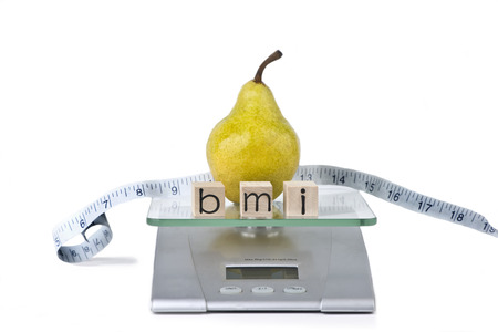 Pear with measuring tape on food scale.