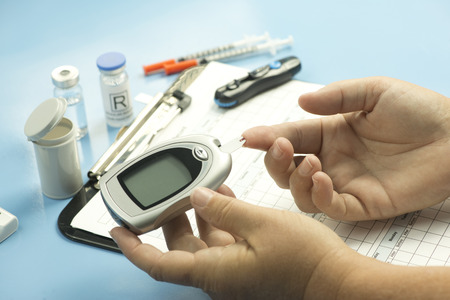 Blood sugar finger stick test with glucometer and diabetic supplies.