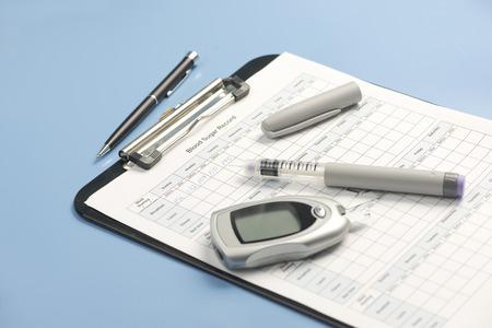 portapapeles: registro de azúcar en la sangre con la pluma de insulina y el glucómetro. Documento creado por el fotógrafo. Foto de archivo