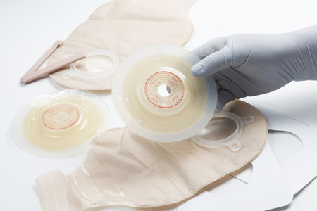 Nurse prepares ostomy supplies for use with patient.