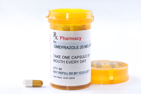 ulcer: Omeprazole prescription bottle with side effects info sheet.  Omeprazole is a generic medication name and label was created by photographer. Stock Photo