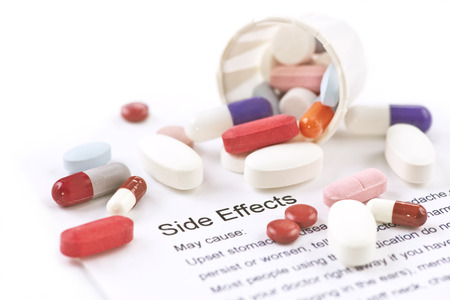 Assorted pills and capsules with side effects information sheet. Archivio Fotografico