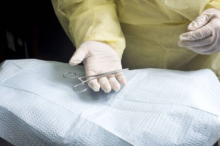 Surgeon accepts hemostat held over sterile draped mayo stand.