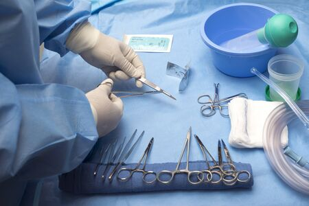 Surgical technician loads scalpel with surgical blade on sterile table. Reklamní fotografie - 131136547