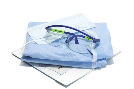 Gloves, mask, gown and goggles for personal protection on white background.