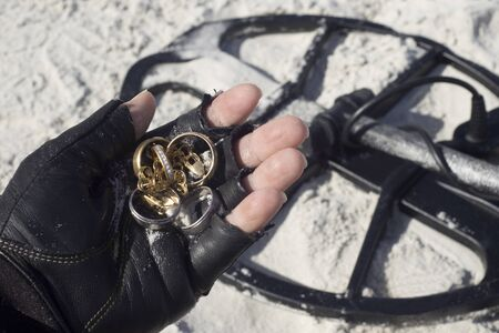 Metal detectorist holds jewelry found by metal detector on beach in Florida.