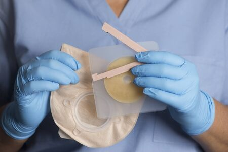 Nurse holds ostomy bag with adhesive wafer and bag clip.