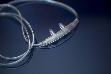 Nasal Cannula and oxygen tubing on blue reflective background. Standard-Bild