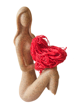 A girl statuette without legs holds a red heart Stock Photo