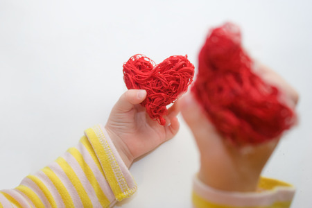 Baby hands holding a red heart. A child plays with red decorative hearts