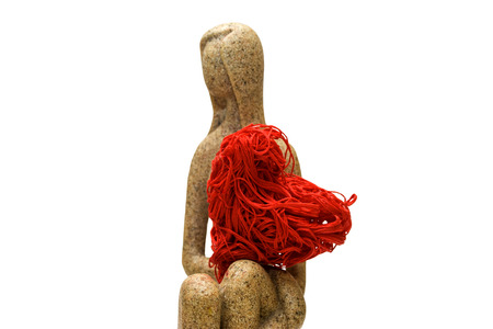 Girl figurine holds a red decorative heart Stockfoto
