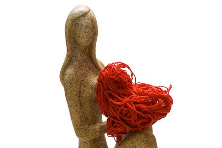 Girl figurine holds a red decorative heart Reklamní fotografie