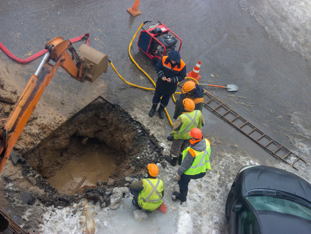 A group of road workers from public utilities in reflective special vests are discussing an emergency when digging a hole to eliminate the leakage of pipes in the middle of winter