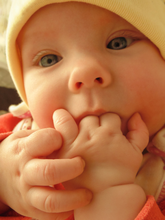 A little baby girl baby sucks her fingers with gusto. The baby put his fingers into his mouth and sucks them in instead of the nipples.