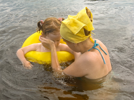 Mom helps her baby girl to wash her eyes from the mote that got there. Do not leave children unattended near the water.