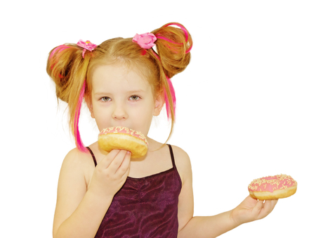 Little happy cute girl is eating donut on white background wall. Child is having fun with donut. Tasty food for playing kids. Funny time  with sweet food. Bright baby girl with pink hair.