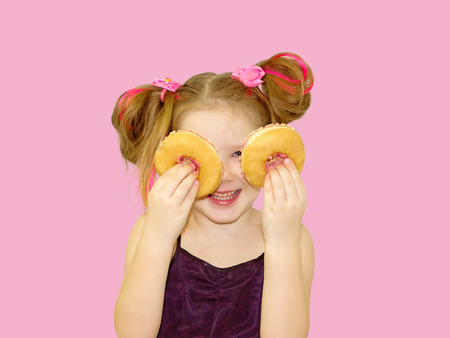 Little happy cute girl is eating donut on pink background wall. Child is having fun with donut. Tasty food for playing kids. Funny time  with sweet food. Bright baby girl with pink hair. Banque d'images