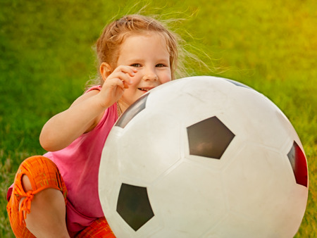 Little baby girl sitting with a huge ball of football colors. Baby is growing and becoming a little cheerleader of a large European game. 免版税图像
