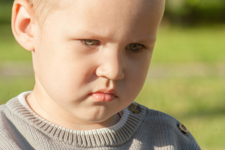 A little toddler boy is upset, sad, focused and serious. The child is offended. Portrait of a beautiful light-eyed boy close-up.