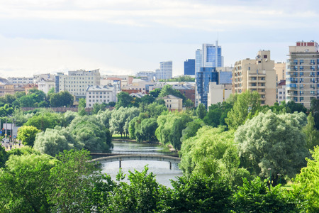 Beautiful view from the height of the spring city center with diverse architecture and a park along the city river.