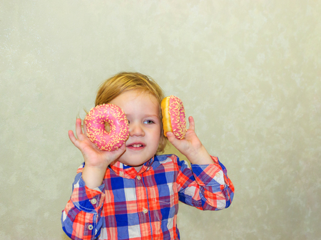 A little kid boy dabbles and plays with two fresh donuts before eating. A child holds donuts near his eyes and looks through the holes like through glasses.