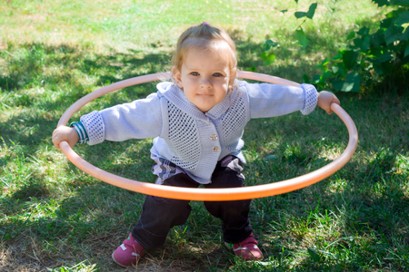 Little baby girl learns to deal with hulahup. The child holds the hoop with two hands. Baby is trying to twist the hoop around the waist. Girl dabbles with a hoop and smiles.