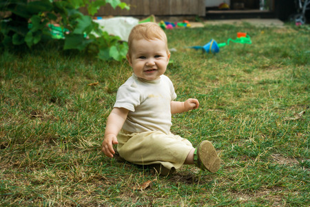 Little toddler boy trains his skills in crawling and sitting. The child happily crawls and sits on the green grass. Toddler smiles and moves on all fours around the yard in the open air. 스톡 콘텐츠