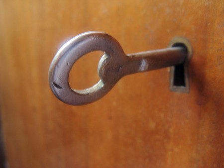 An old antique key reveals secrets under lock and key. The round key sticks out of the keyhole and is ready to open the door.