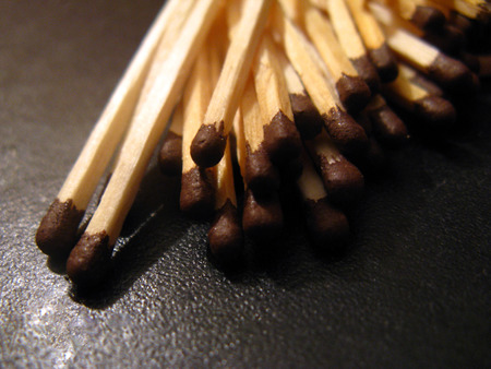 A pile of matches without a box lying on the artificial leather. A group of unused matches scattered on the leather surface of the sofa.