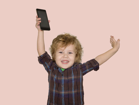 A little toddler boy picks up a smartphone gadget above his head. A satisfied child is happy that he was allowed to play phones with his smartphone.