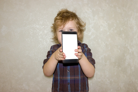 The little boy is hiding behind the phone. The child shows a blank white phone screen. Kid looks out from behind the smartphone with interest.