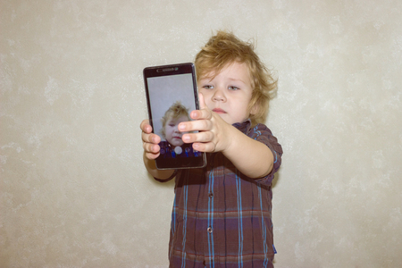 A boy kid looks into the camera of a smartphone, shows the screen with his digital photo. Toddler smiles at the camera and takes a selfie.