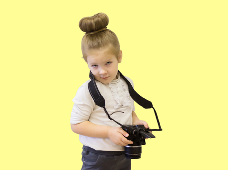 A little girl in business clothes holds a reflex camera in her hands. The child learns to take pictures and learns the difficult technique in his hands. Stock Photo