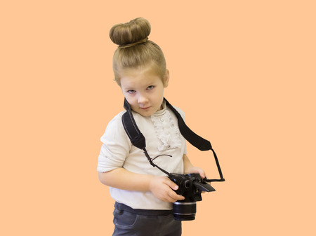 A little girl in business clothes holds a reflex camera in her hands. The child learns to take pictures and learns the difficult technique in his hands. Archivio Fotografico