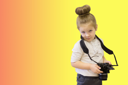 A little clever girl in business dress holds a reflex camera in her hands. The intelligent child learns to take pictures. Reklamní fotografie