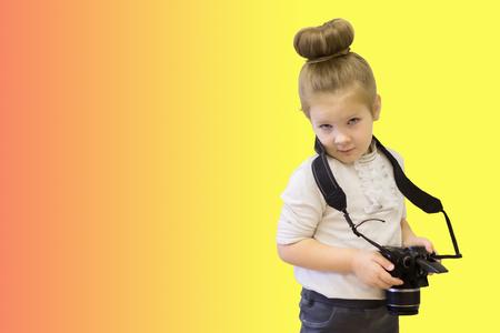 Una niña inteligente en traje de negocios tiene una cámara réflex en sus manos. El niño inteligente aprende a tomar fotografías. Foto de archivo