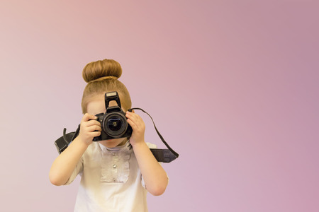 A smart preschooler girl holds a reflex camera in her hands in front of her face. The kid wants to take a picture. The junior holds her finger on the shutter button.