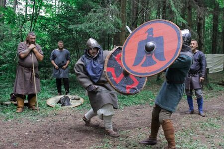 Grodek, POLAND - JULY 13, 2019. The medieval duel of two Viking warriors. Spectators in  Middle Ages robe watching battle of armed people. Match is held according to rules.
