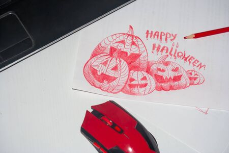 Jack pumpkin sketch, pencil, mouse and laptop are on the desk. A draft for creating a Halloween greeting card design has been prepared for transferring to a computer.