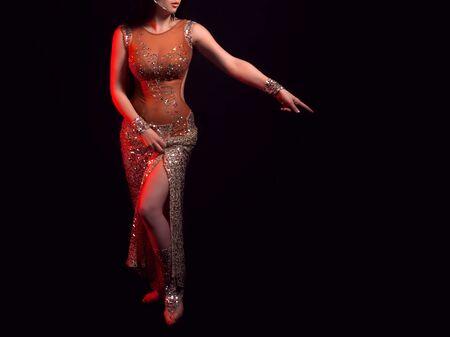 Der Körper eines schönen Mädchens in einem Perlenkostüm für Bauchtanz auf schwarzem Hintergrund. Eine Frau steht im Licht roter Scheinwerfer. Das Mädchen zeigt mit dem Finger auf etwas. Standard-Bild