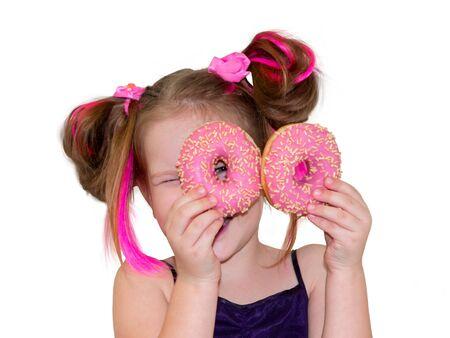 Ein kleines Mädchen mit rosa Haaren steht und hält zwei Donuts wie eine Brille in der Nähe ihrer Augen. Frohes Mädchen lächelt einen köstlichen Donut an.
