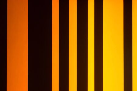 The gradient of the vertical stripes of orange and black alternate. Photo fragment of urban illumination close-up.